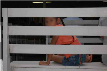 Native girl looks through bench slats
